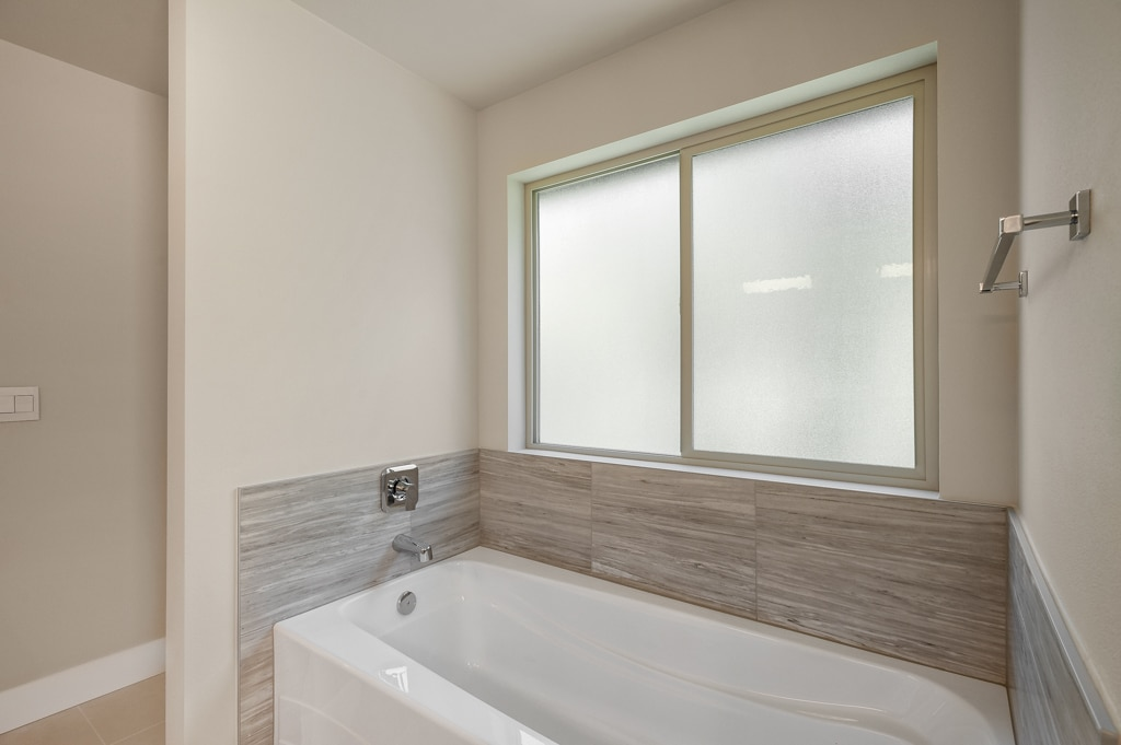 Soaking tub with opaque privacy glass window above