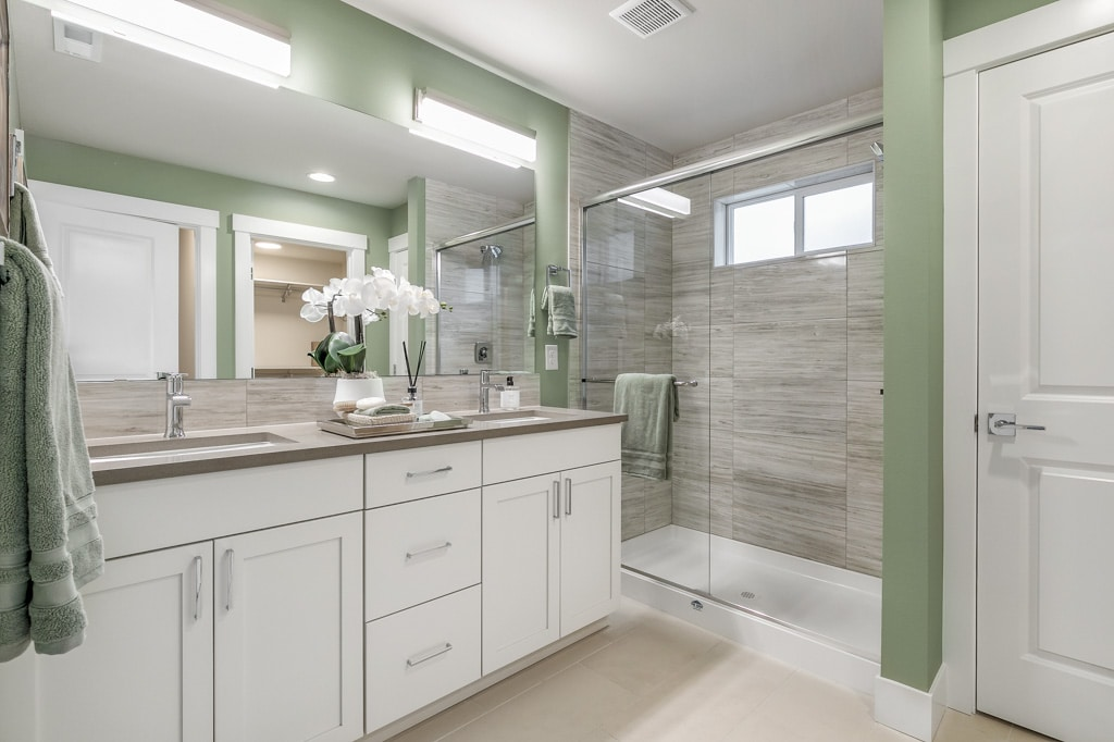 Walk-in shower has full-height tile and opaque privacy glass windows