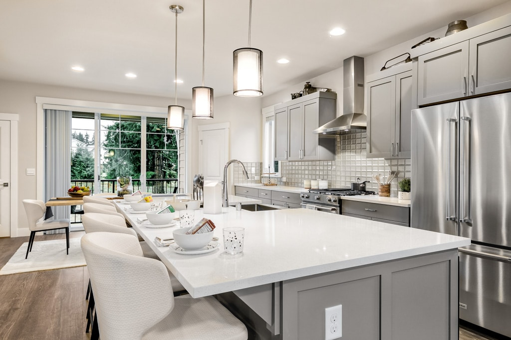 Slab quartz-topped work island with pendant lights above