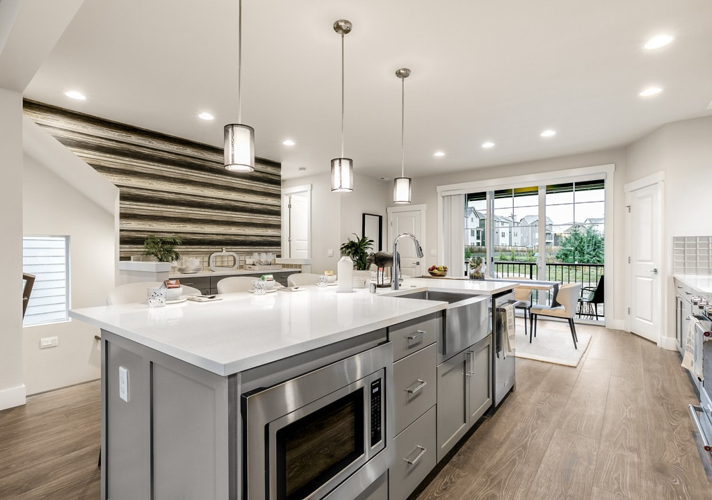 Work island has under-counter convection microwave, farmhouse sink and touchless faucet
