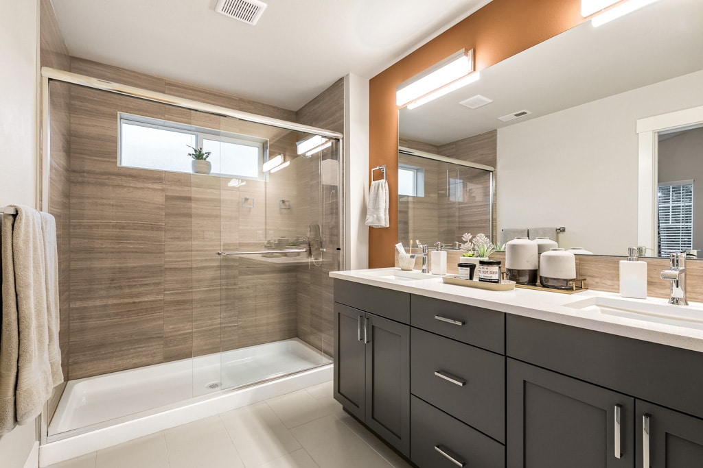 Ensuite bathroom with dual-sink vanity and full-height tile in the walk-in shower