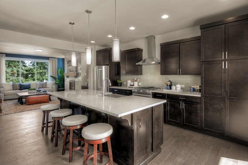 Eat-in kitchen work island with slab quartz countertops and pendant lights.