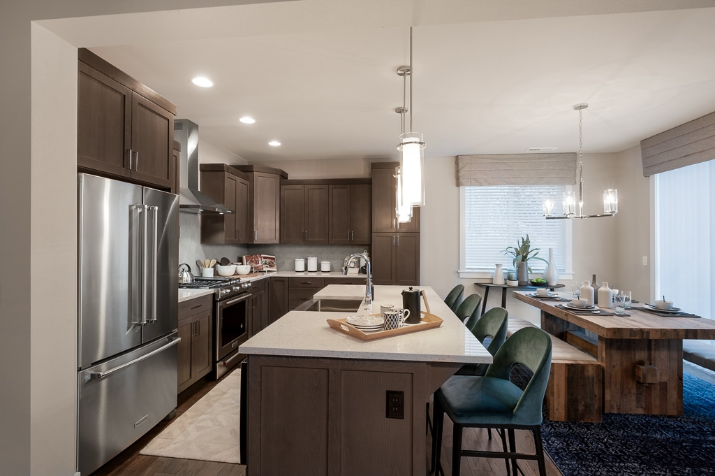 Kitchen with work island topped with slab quartz and adjacent dining room