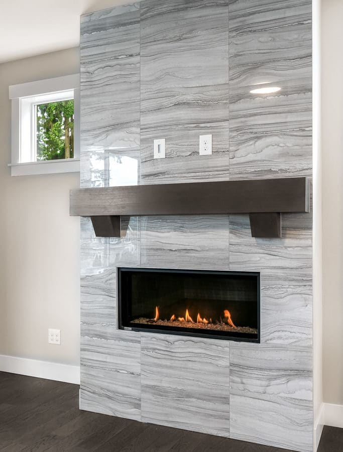 Gas fireplace has full-height tile surround