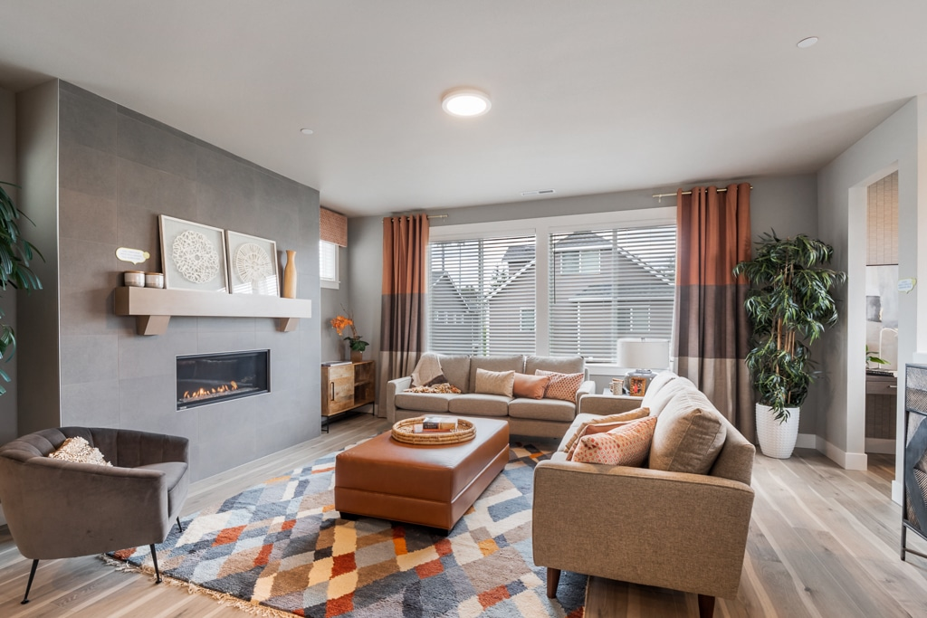Living room centers around gas fireplace with ceiling-height tile and wood mantel