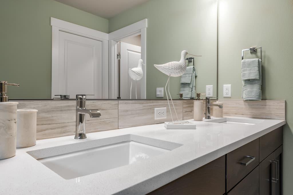 Dual sink vanity with slab quartz countertops in primary bathroom