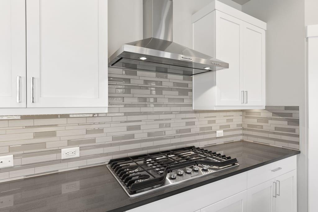 Gas cooking, stainless steel rangehood and full height tile backsplash
