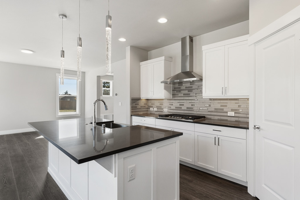 Crisp and bright kitchen with slab quartz countertops and big work island